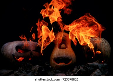Three Very scary and dangerous Halloween pumpkins, with a threatening look and a grinning villain, in the darkness on a wooden pallet, with leaves spewing flames of fire