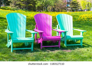 Three vibrant color seats in a public park overlooking lake Ontario. The area is a relaxation place for city dwellers and visitors.