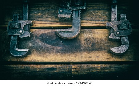 Three Vintage Pipe Wrenches on a Rough Wood Background