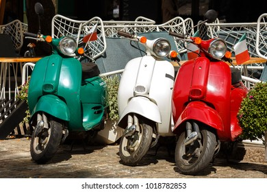 Three vintage scooter Italian flag colors parked on a city street at sunny sammer day.