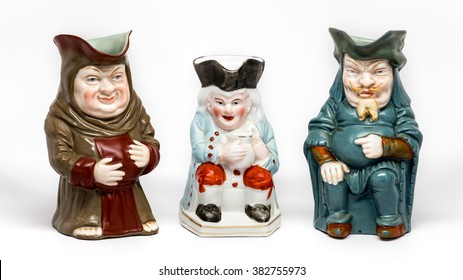 Three vintage Toby jugs on white background