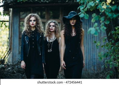 three vintage women as witches, pose in front of an abandoned building on the eve of Halloween