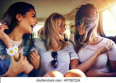 Three vivacious young women in the back of a car laughing and joking as the winds blows their long hair over their faces as they travel