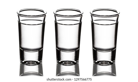 Three vodka shot glass row isolated on white.