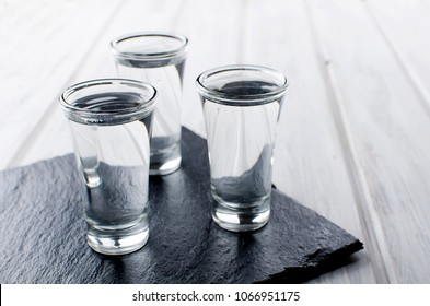 three Vodka shots with ice on black stone board on white wooden table, copy space