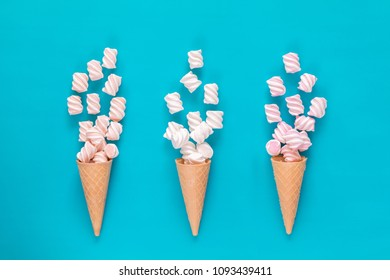 Three waffle cone with marshmallow bouquets on blue surface. Flat lay, top view sweet food background.