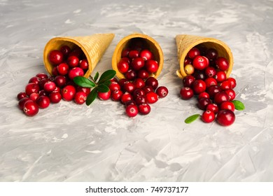 Three waffle cones with fresh red cranberry over grey background