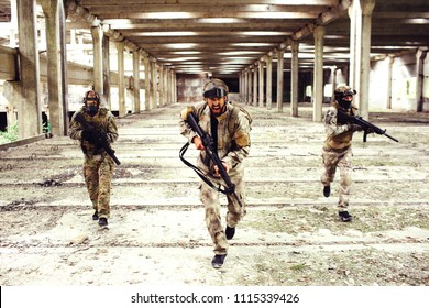 Three warriors with equipment is running down big and bright room. Two of them are looking to the sides while the man in front is looking straight and screaming. All of them have rifles in hands.