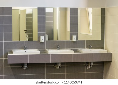 Three washbasins with mirrors