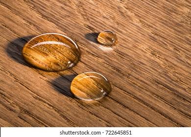 Three water beads on finished oak wood. Horizontal image.