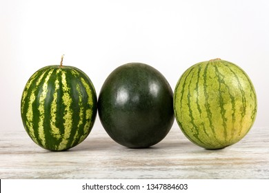 Three watermelons of different varieties, green and striped on a white background. Isolated, view straight, place for text.