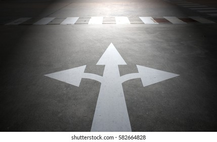 Three way arrow signs on the road with lighting