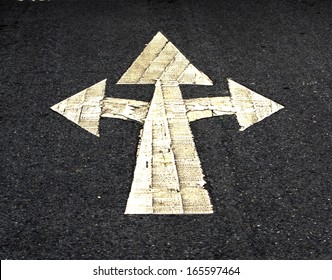 A three way arrow symbol on a black asphalt road surface.