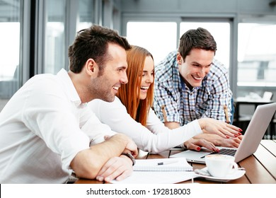 Three web designers looking at a laptop screen