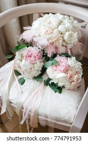 Three wedding bouquets mae of white and pink flowers with ribbons and feather lie on the chair