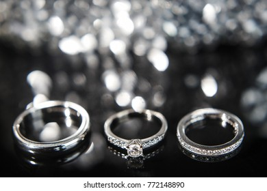 Three wedding rings on the reflecting surface with highlights.