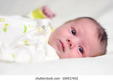 Three Week Old Baby Boy. Infant laying on white blanket looking at viewer. Shallow DOF.