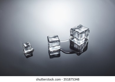 three wet ice cubes on gray tone background