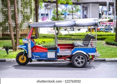 A three wheeled tuk tuk taxi on a street in the Thai capital
