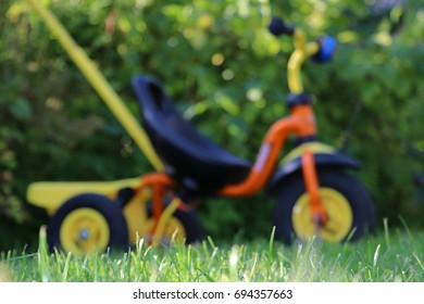 Three wheels children's bicycle on the garden, blurred