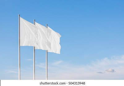 Three white blank flags waving in the wind against cloudy sky. Perfect mockup to add any logo, symbol or sign