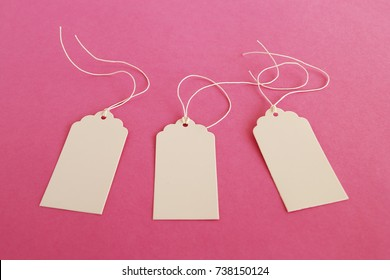 Three white blank paper price tags or labels set on the pink background.