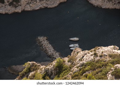 Three white boats in the blue calm water in a bay Calanques in the national park in Marseille in France between white rocks with green grass. Parc National des Calanques
