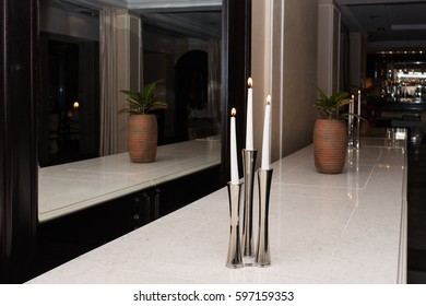 Three white burning candles in an iron candlestick. A pot with greenery. Mirror. Reflection