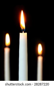 Three white candles, burning in the darkness.  Focus on front candle, shallow depth of field.