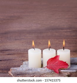 Three white candles on wooden background