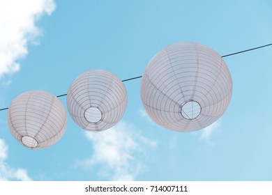 three white Chinese lantern, lampion, hanging on rope in wind, against blue sky