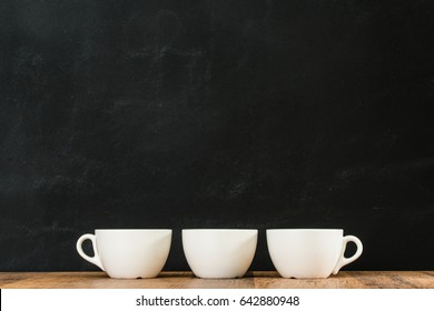 three white coffee cups arranged together placed on retro wood texture floor with black chalkboard wall background in restaurant studio.