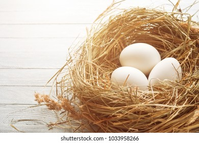 Three white eggs in the hay nest