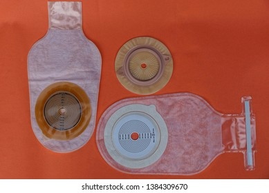 three white empty medical colostomy bag on a red table