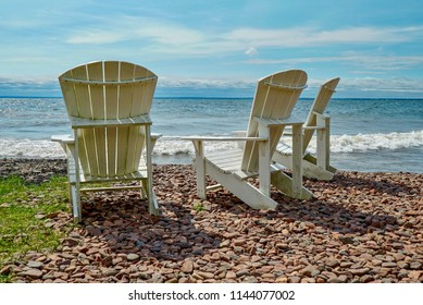 Three White High Back Lawn Chairs on the Rocky Shore of Lake Superior in Northern Minnesota, Waves, Blue Sky, Clouds, Sunny