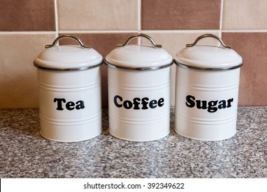 Three white metal canisters for storing tea, coffee and sugar on a granite kitchen worktop with brown and beige tiles in the background.