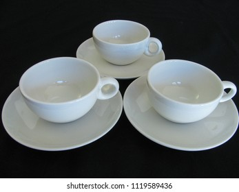 Three white mid century modern ceramic coffee cups and saucers on a black limbo background