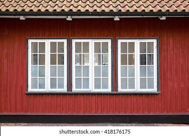 Three white painted casement windows with partly frosted glazing, in a red painted wood plank facade