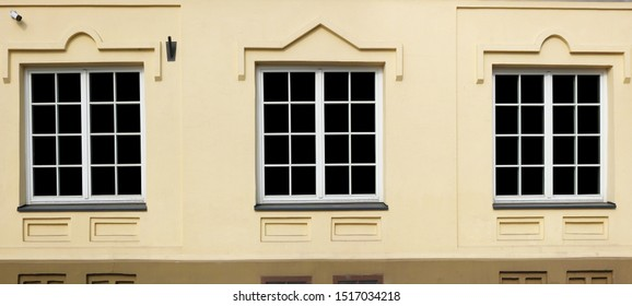 Three  white  plastic windows in the restored ancient old city  house. Glass isolared on black. Panoramic outdoor  urban shot