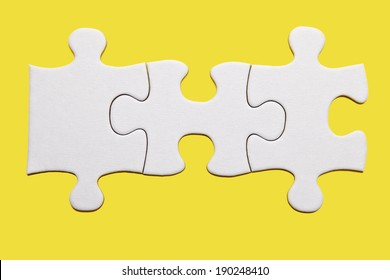 Three white puzzle pieces on yellow background