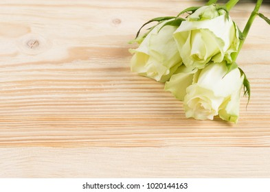 three white roses lie on a wooden background, place for an inscription