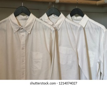 Three white shirts hanging in closet