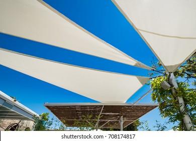 Three white sun shades in a spanish beach club. Urban scene in a Mediterranean tourism spot under blue sky on a sunny day