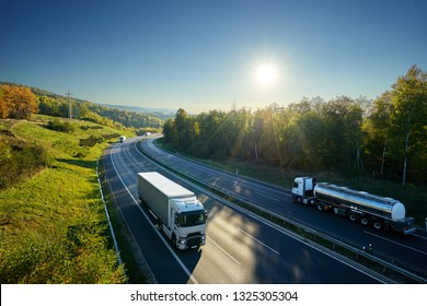 Three white trucks and chrome tanker driving on the asphalt highway between deciduous forest under the rays of the sun. View from above.
