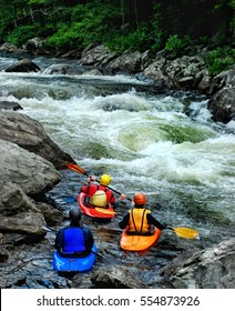 Three whitewater kayakers waiting to surf a wave in fast moving water on the river