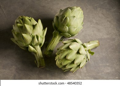 Three whole artichokes on marble surface