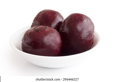 Three whole cooked beetroots in white dish isolated on white.