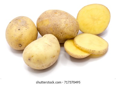 Three whole potatoes and slices isolated on white background