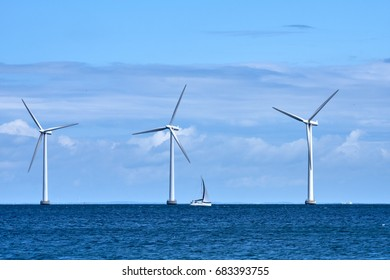 Three wind mills standing offshore at sea near Amager Beach Park in Denmark, with a sail boat sailing in front