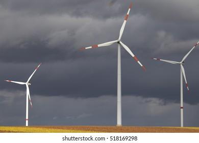 Three wind turbine generators in wind farm in Germany on dark cloudy sky background on gloomy day